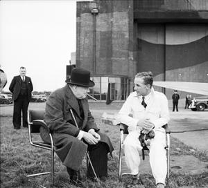 Alex Henshaw talking with Prime Minister Winston Churchill at Castle Bromwich after a Spitfire demonstration in 1941. Image from the Imperial War Museum online collection now in the public domain.