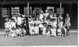 Colin Tooley at Hodge Hill Infants School 1948; Colin is standing by the lefty-hand pillar wearing a pointed clown's hat. Photograph from a contributor to the Birmingham History Forum.